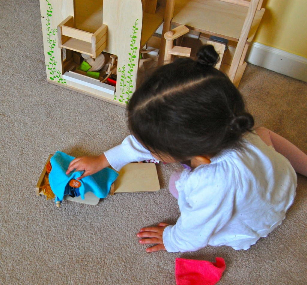 baby tucking in dolls at dollhouse