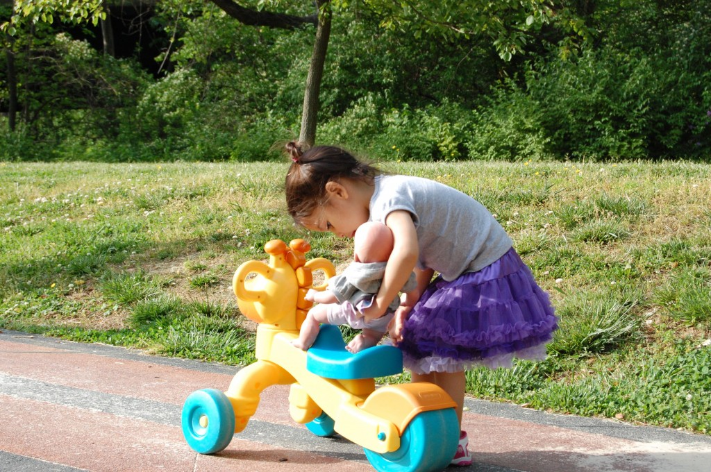 little girl pushing baby doll at the park