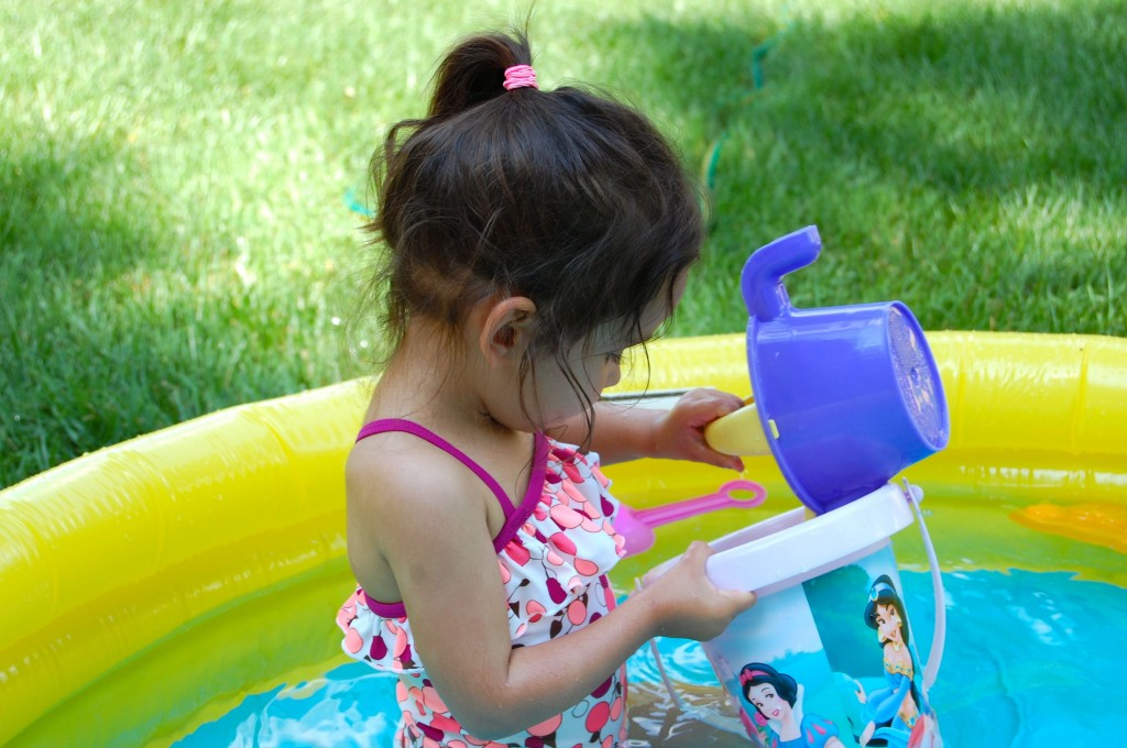 little girl pouring water in the pool