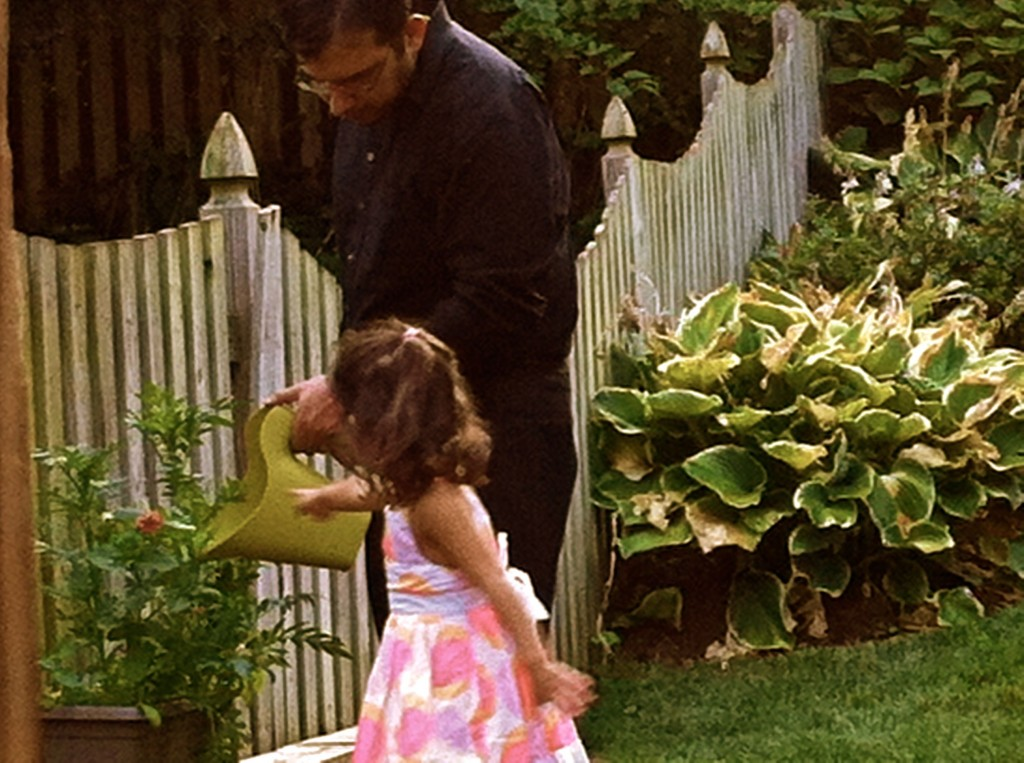 little girl and daddy watering flowers