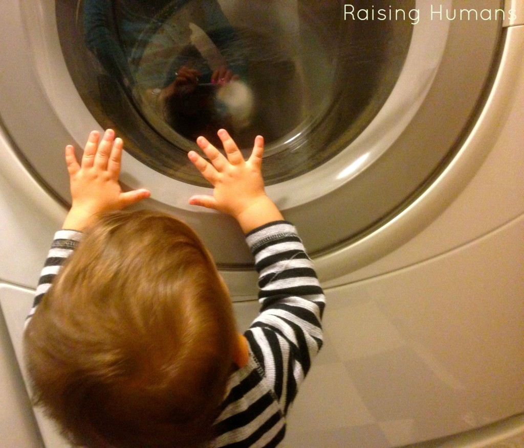 baby boy looking at the dryer